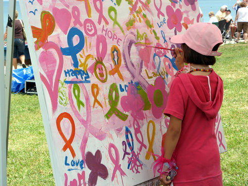 little girl painting on breast cancer mural