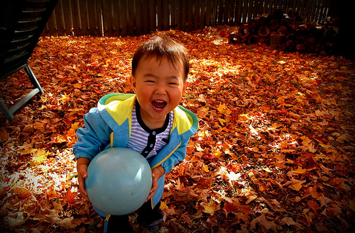 child in fall leaves