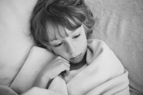 boy wrapped in blanket watching TV television