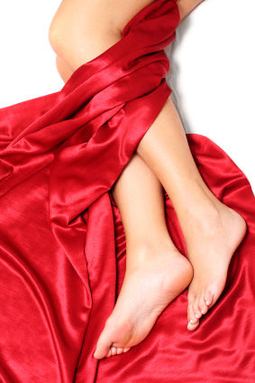woman's leg with red silk sheets