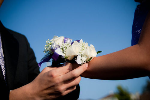 teen boy putting corsage on date's wrist