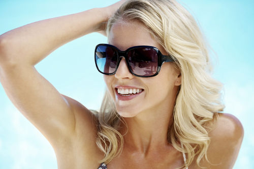 woman sunglasses pool summer multitasking beauty products