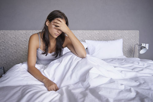 woman in bed having regrets