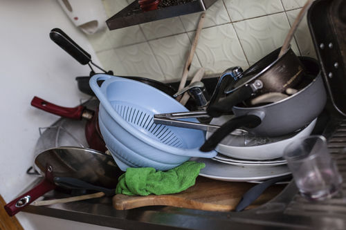messy sink full of dirty dishes