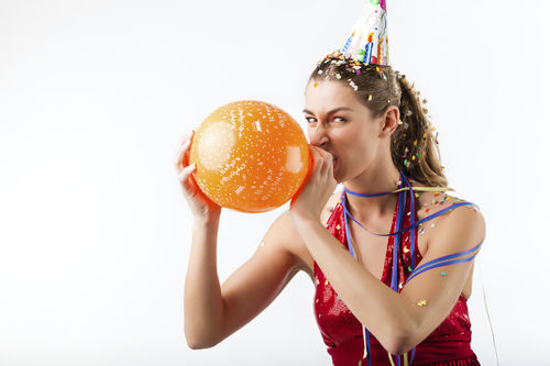 annoyed woman blowing up birthday balloons