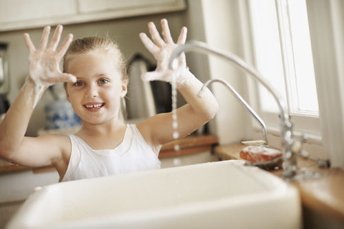 little girl washing her hands in the sink