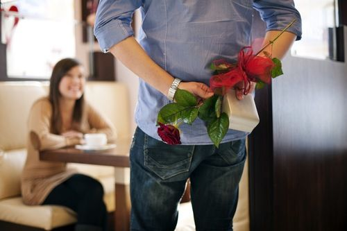 man surprising his wife or girlfriend with roses