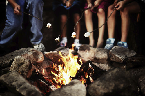family roasting marshmallows at a campfire