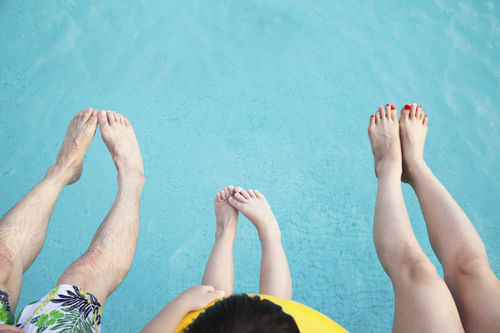 family feet in the pool