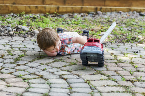 boy playing outside with a toy truck