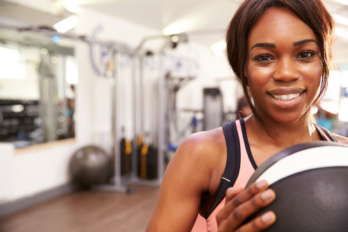 Portrait of a smiling woman holding a medicine ball at a gym
