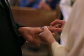 woman placing wedding band on husband's finger marriage vows