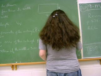 woman writing on chalkboard in a math class